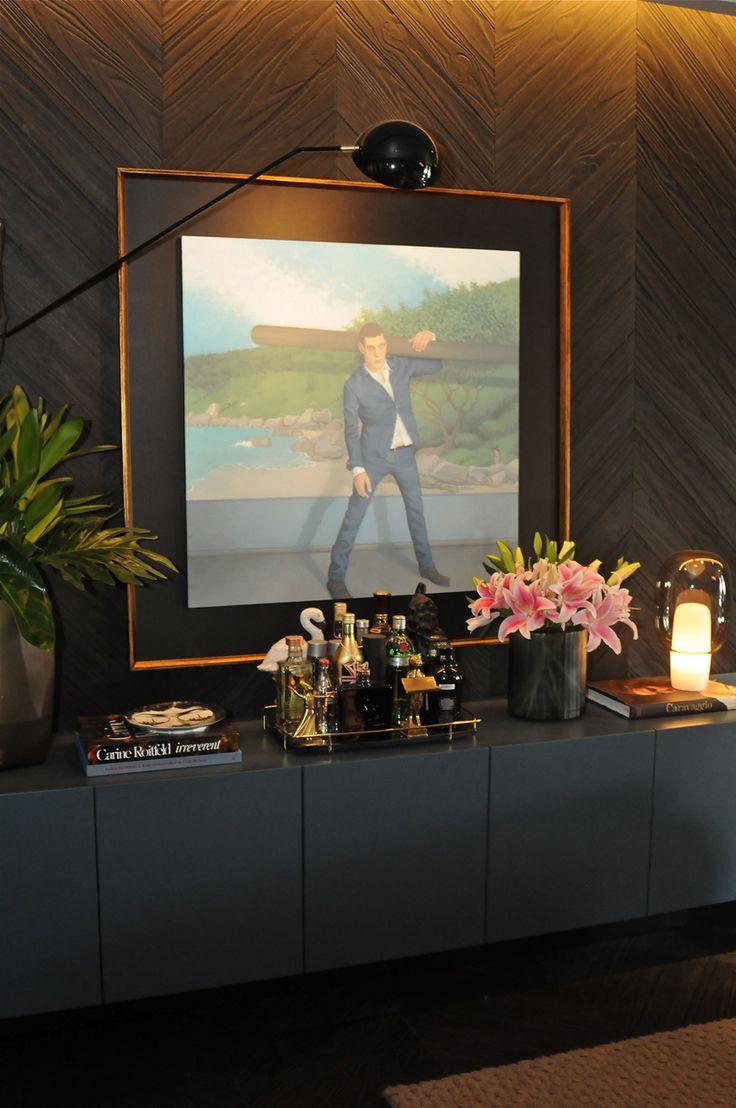 Casa Cor 30 anos | Almoço de sexta - projeto de uma sala com uso de painel de madeira e móveis pretos. a iluminação destacou bem os móveis e para decorar quadros, vasos com flores e livros