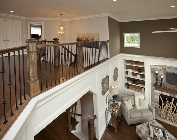 Open Second Floor Railing Overlooking Great Room by 3 Pillar Homes. Our craftsmanship is shown again in this home with crown molding, our Signature Archways, built-ins and oversized baseboards.