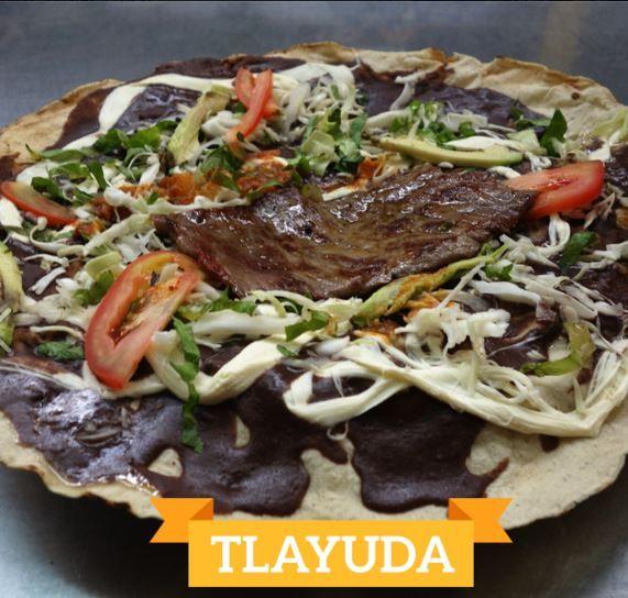 La tlayuda es originaria de Oaxaca, lleva un asiento de chicharron ( lo que queda en el fondo cuando frien los chicharrones ) frijol, queso de hebra, cecina y demas ingredientes al gusto.