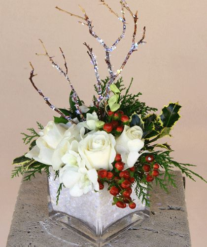 HOLIDAY IN THE SNOW -  Gorgeous blooms of hand-chosen white Roses, White Dendrobium Orchids imported from Thaliand, Holly, EVergreens, and branches decorated with snow, artfully arranged in a simple and elegant, heavy glass cubed vase.