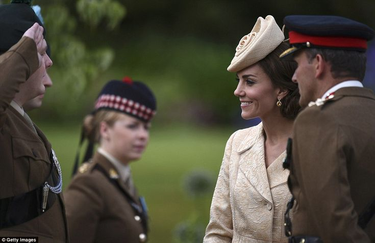 The Duchess seemed ever charming as she made her way along a line of soldiers with each of...