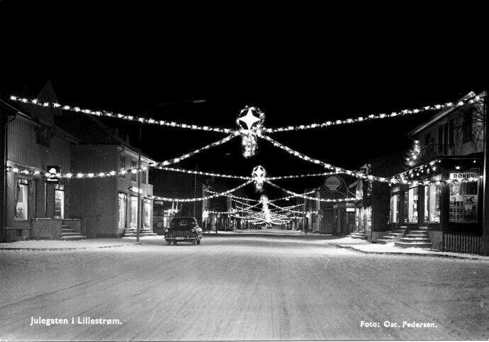 Akershus fylke Skedsmo kommune Lillestrøm Storgt Julegata 1957 Foto Oscar Pedersen. Krysset Parkalleen Storgaten. I 1956 var juletreet på plass med belysning, nederst i storgaten. Julegaten ble satt opp for første gang i 1957 med 3200 lyspærer i julestasen. Bokbutikken til høyre, på kortet fra 1957, ble landets første selvbetjente bokhandel. Den ble åpnet av Hactor Enes Køhn i 1949.