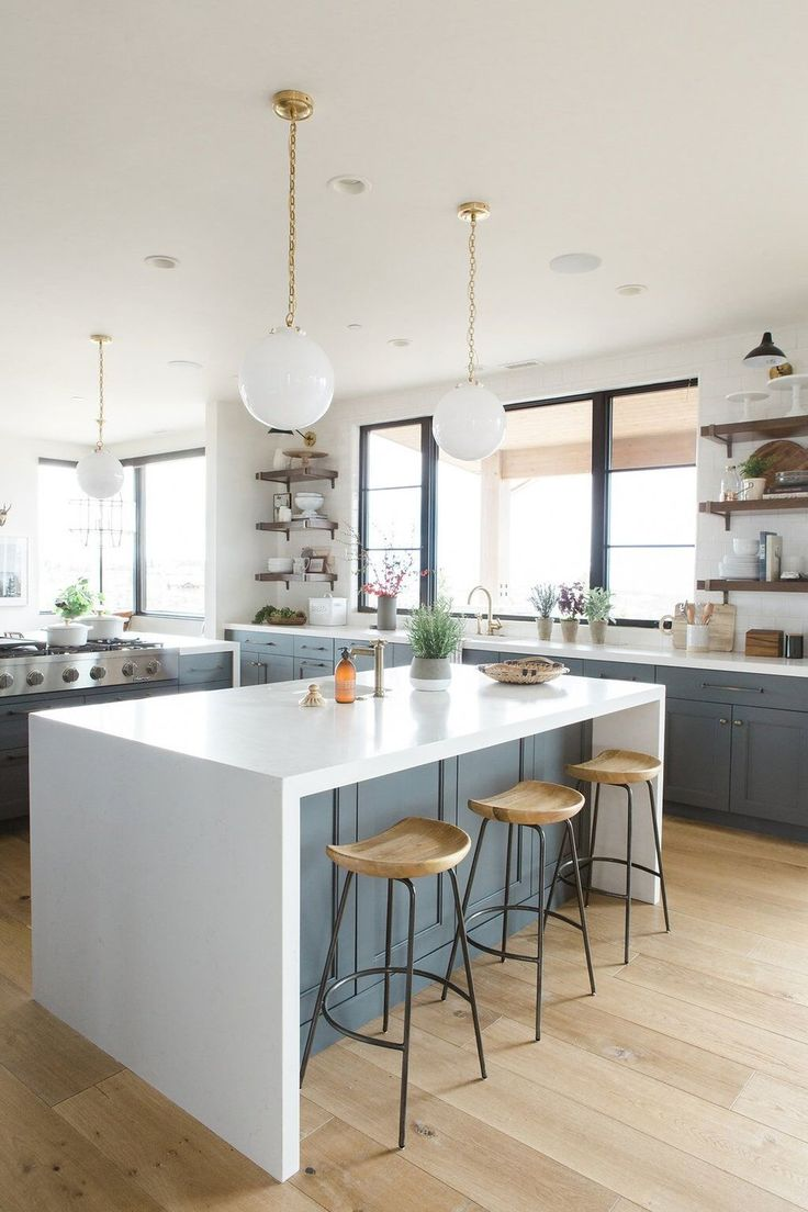Modern kitchen with deep walnut open shelves, natural wood bar stools and white waterfall edged countertops