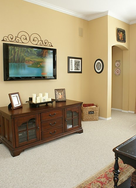 i like the iron work decor above the tv! And love the wall color! Very close to the color I wanna paint my downstairs