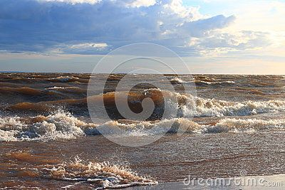 Surf wave rolls on a sandy beach in the Neva Bay on a cloudy evening. Saint-Petersburg, Russia