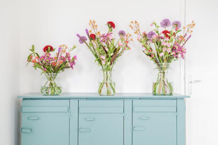 Boeket bloemen van verschillende formaten in glazen vazen op een blauwe kast | bouquet of flowers in different sizes | Bloomon