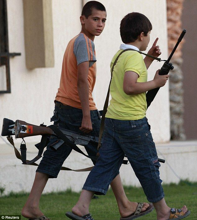 Boys help rebel fighters carry automatic weapons in Misrata, Libya, after a gun battle with Gaddafi troops