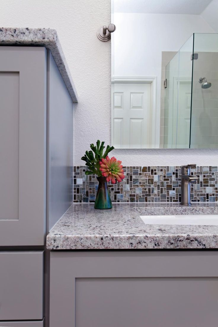 Flecks of color in natural stone countertops emulate the intrigue and sparkle in the glass mosaic tiles to create an elegant and soothing transitional master bathroom.