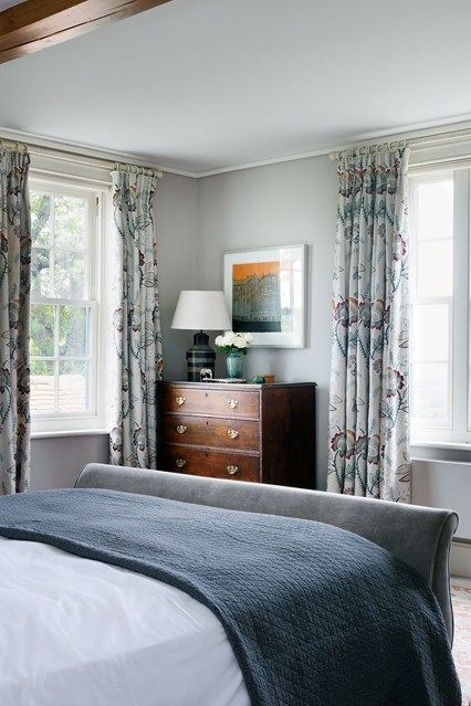 Blue Farmhouse Bedroom  in Country Bedroom design ideas - modern room with floral curtains and double bed, antique chest of drawers.