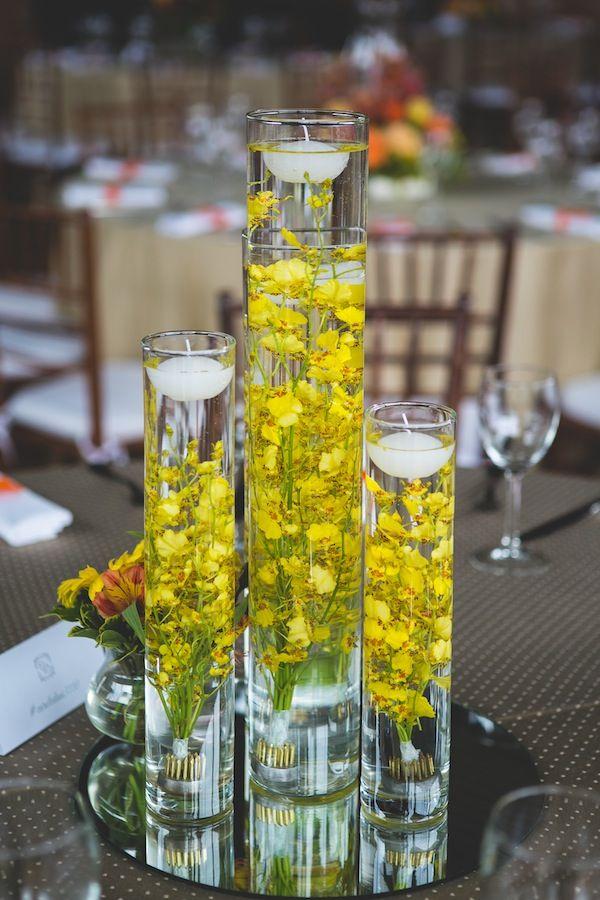 Centro de mesa amarelo, feito com orquídeas chuva de ouro imersas em água e vela flutuante. Foto: Adriana e Patricia