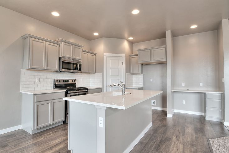 Drop dead gorgeous kitchen! Cabinets: Gray, Manchester, Maple, Cloud Backsplash: 3x6 White Subway Tile, Brickset, with Oyster Gray Grout Kitchen Countertops: Woven Wool Engineered Stone Flooring: Woodland Maple Branch Laminate #Whitesubwaytile #EngineeredStone