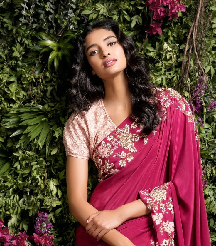 Paired with a blush pink shell net blouse, this saree has intricate detailed flowered on the edges.