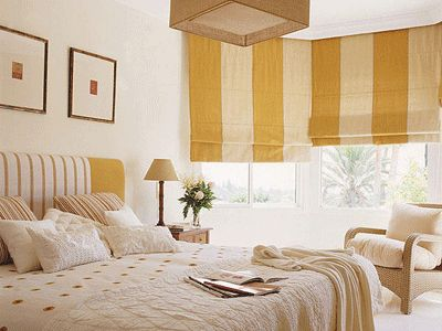 This wide vertical striped flat roman shade adds a a hint of playfulness to this bedroom.
