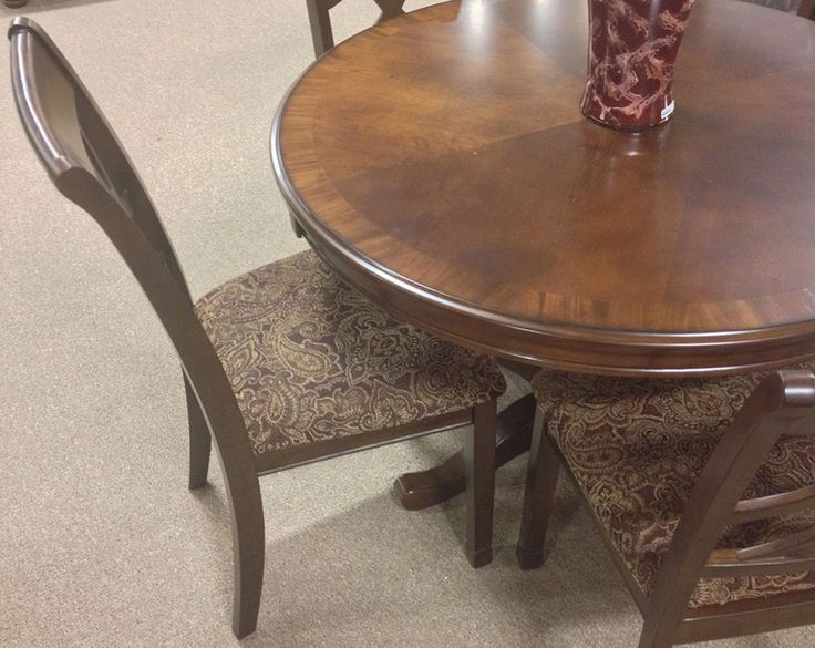 THE LEAHLYN ROUND DINING TABLE SET The Upholstered Side Chairs For Seating Have Elegant Fretwork With A Central Diamond Motif On Chair Backd And