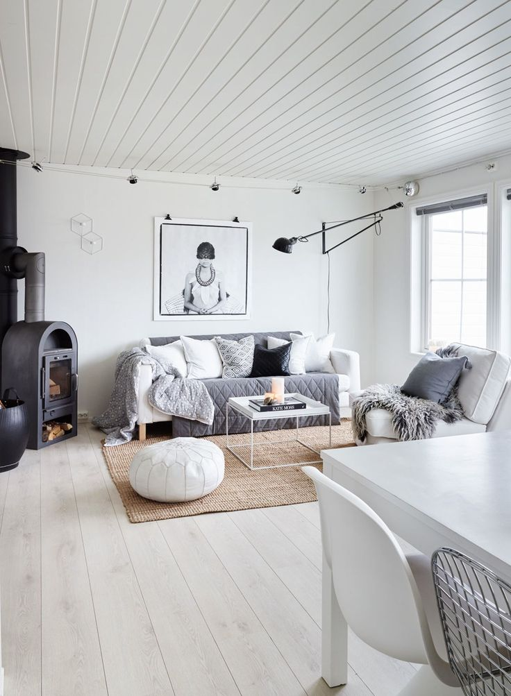 Stuen har en monokrom men likevel varm stil med sofa og gulvteppe fra Ikea, bord fra Hay, grått pledd fra Ellos og marokkansk puff fra Lille Medina. Bildet fra Love Warriors lyses opp av Flos 265-lampen.