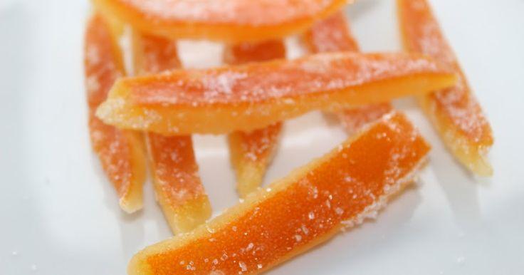 Receta de cáscara de naranja confitada.  Resultan deliciosas bañadas en chocolate negro o simplemente solas envueltas en azúar.  La misma técnica puede emplearse para hacer cáscara de limón confitada o confitar la piel de cualqueir cítrico.