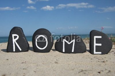 Rome, capital of Italy, souvenir on black stones with beach background