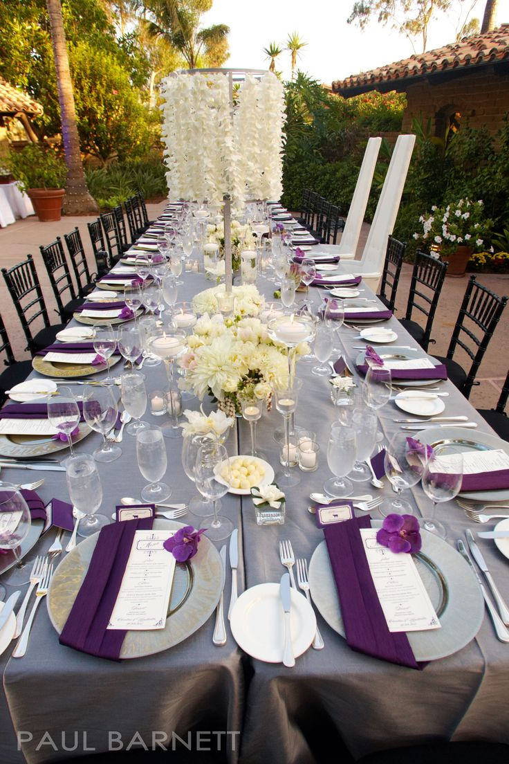 Extravagant tablescape of white, purple and grey - love the napkin fold over the plate with the menu tucked in and a blossom accentuating the palette.