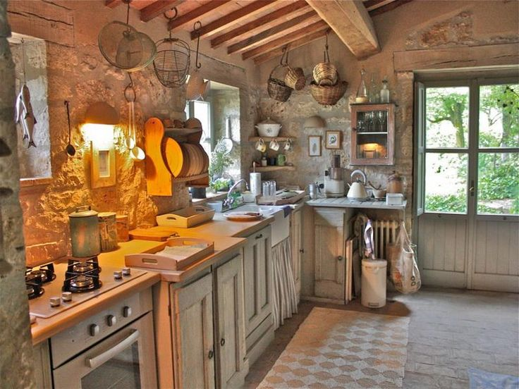 french country small kitchen with rough stone walls and farmhouse sink