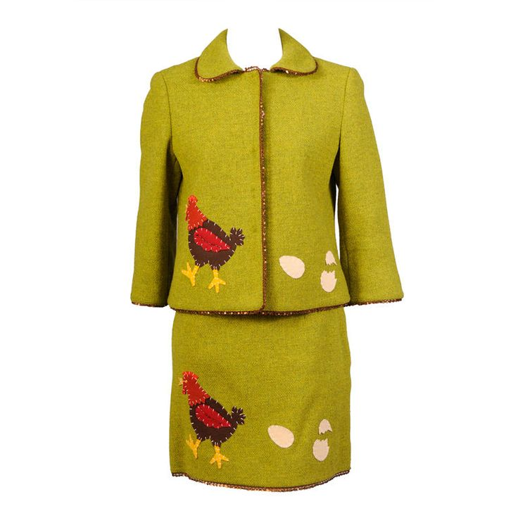 Suit in bright green wool, outlined with copper colored sequins | Italy, 1980's | A wonderfully whimsical suit from Franco Moschino poses the eternal question 'Which came first, the chicken or the egg?' | Felt appliqued chicken, accented with beadwork and embroidery. On the other side of the jacket and skirt are the eggs. The jacket closes with oversized felt covered snaps