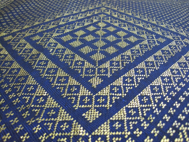 Photograph of vintage black & bronze/gold color assiut - it's placed on top of blue fabric
