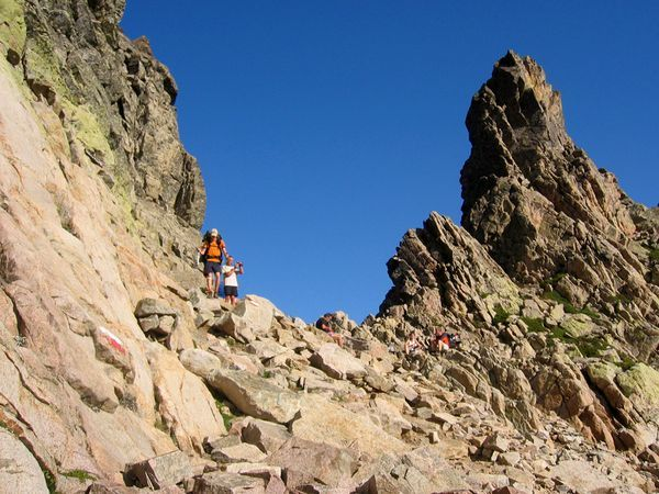 Hikers make their way across the rocky GR 20 in Corsica, France.