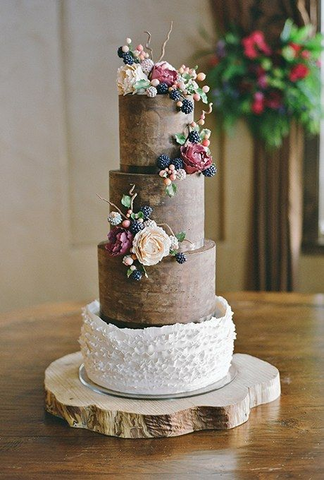 To complement the bride's earthy yet sophisticated wedding aesthetic, Sonja McLean of Sweet and Swanky Cakes made this rustic-looking cake, which took more than 80 hours to create. Chocolate ganache was applied to the tiers to achieve a wood-grain effect, while the ruffles added a romantic touch. The entire cake was covered in peonies, ripe blackberries, twigs, and hypericum berries, all sculpted from fondant and sugar.