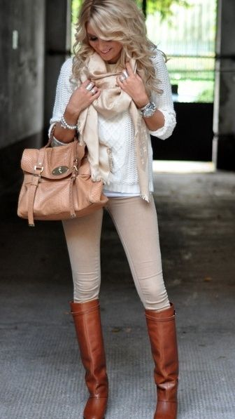 Tan knee-high boots, beige pants, white sweater with cream scarf. Tan purse with silver watch.