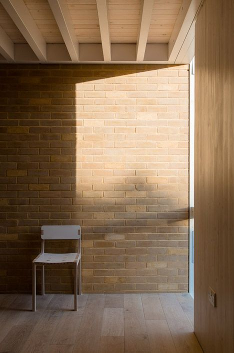 The sloping roofline of an old extension to a London residence is surrounded by the pale brickwork of its replacement