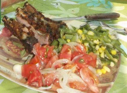 costillar de cerdo asado, porotos verdes (judías), choclo (maíz) y ensalada a la chilena (tomate, cebolla y cilantro)