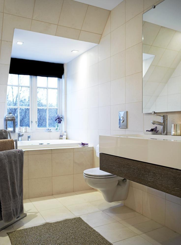 Den varmhvite bakgrunnen på veggene og i store flisflater rammes inn av svarte senkegardiner og den mørke treflaten i servantbenken. Fargekontrasten skaper spenning i en harmoni, som ellers kunne blitt ensformig og kjedelig. Badekaret er plassert i vindusfanget, slik at du kan følge årstidene under morgenstellet. Det innebygde badekaret g det vegghengte toalettet gjør også renholdet lettere.