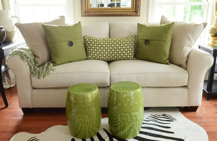 Pillow arrangements sofa with green pillows and a multicolored green throw