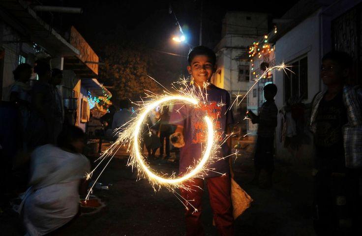A boy waves fireworks during Diwali, the Indian festival of lights.