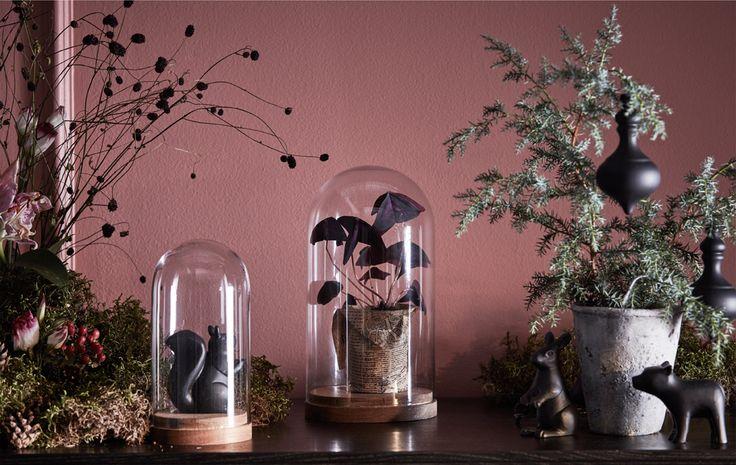 Skrinka ozdobená zeleňou, kvetmi a sklenenými krytmi.