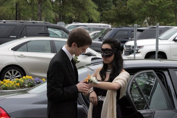 Opening the door and presenting her corsage.