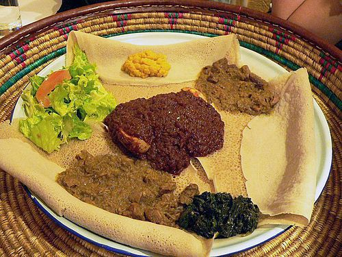 This meal, consisting of injera and several kinds of wat or tsebhi (stew), is typical of Ethiopian and Eritrean cuisine.
