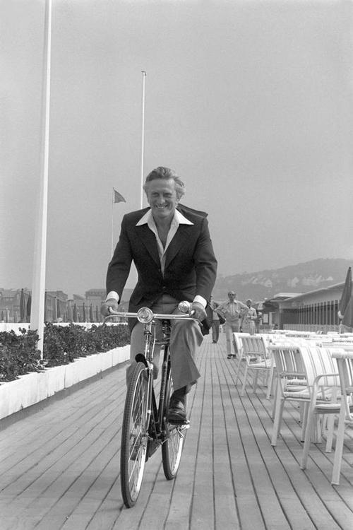 Kirk Douglas rides a bike.