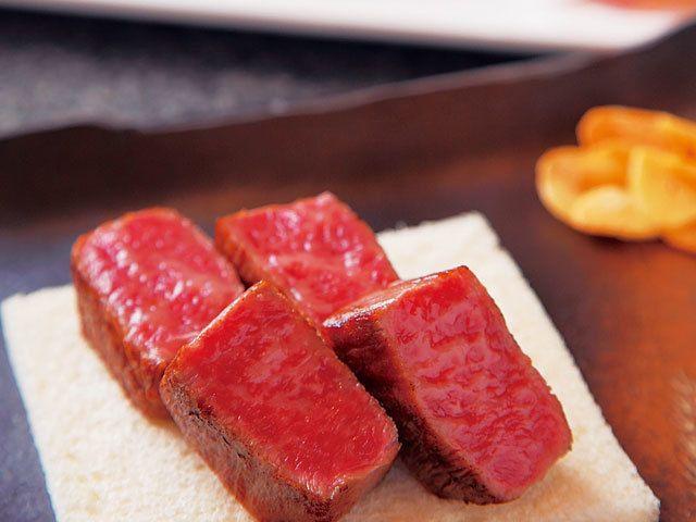 《 銀座 》宮崎牛ロースステーキランチ 写真はしっとりとした食感が魅力のステーキ。小鉢、前菜、デザートなどもセットに。¥7,000  高級和牛「宮崎牛」を鉄板焼きで  『銀座みやちく』  銀座  和牛の3大ブランドのひとつ宮崎牛。ここは宮崎JAを母体とする会社『みやちく』直営の鉄板焼き店とあり、現地より直送された高級牛を比較的リーズナブルに楽しめる。もちろん自社の肉はすべて高い衛生基準をクリアしたもの。   美しい霜降りが入った肉はもちろん、旬の宮崎食材を豊富に織り交ぜたコースは、カウンターを備えた個室でも楽しめる。充実の設備は接待などにも重宝すること間違いなし。