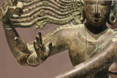 a close up of a bronze statue of the Hindu god Shiva, the destroyer. in one hand he holds the flames that will destroy at the end of time, and in the other he holds the drum that beats with the heartbeat of the universe. He dances atop the physical representation of ignorance.