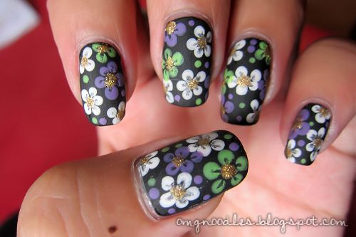 """""""My base color is Wet 'n' Wild Black Creme, the flowers are made using a dotting tool of Wet 'n' Wild French White Creme, China Glaze Spontaneous,  China Glaze Entourage. I used Art Deco 24k Glitter for the center of the flowers  finished this mani off with Hard Candy Matte-ly In Love."""""""