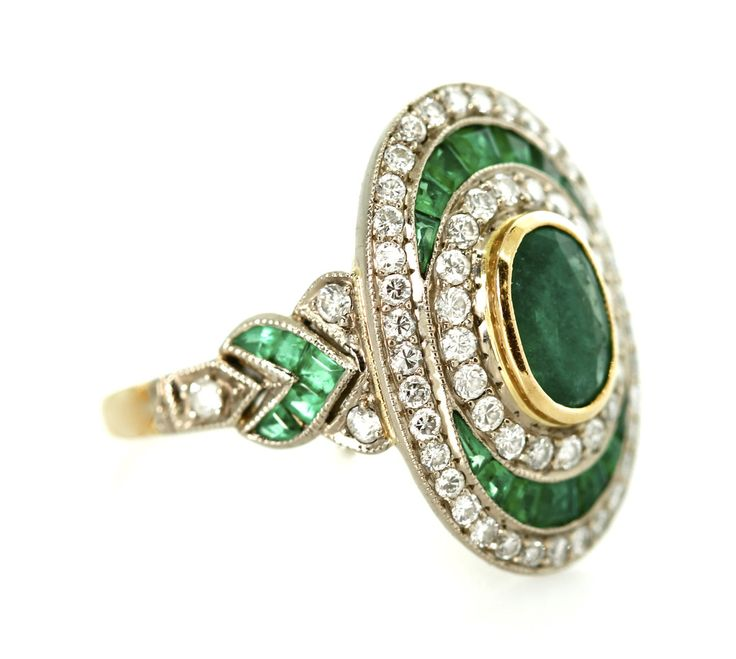Vintage Emerald and Diamond Dinner Ring | Tara Nash Jeweler - Gorgeous 18k white and yellow gold Emerald and Diamond ring with one oval cut Emerald bezel set and surrounded by a double halo of diamonds and a channel set halo of princess cut Emeralds. $2,895.00