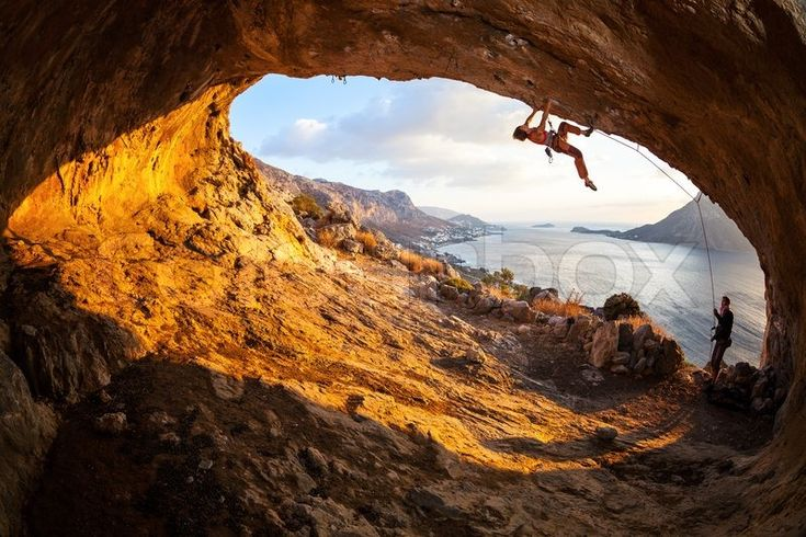 Young woman lead climbing in cave with beautiful view in background | Stock Photo | Colourbox on Colourbox