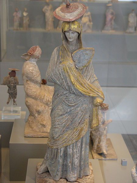 Ancient Greek statue of a lady with blue and gilt garment, fan and sun hat, from Tanagra, 325-300 BCAltes_Museum-Tanagra-lady_with_fan