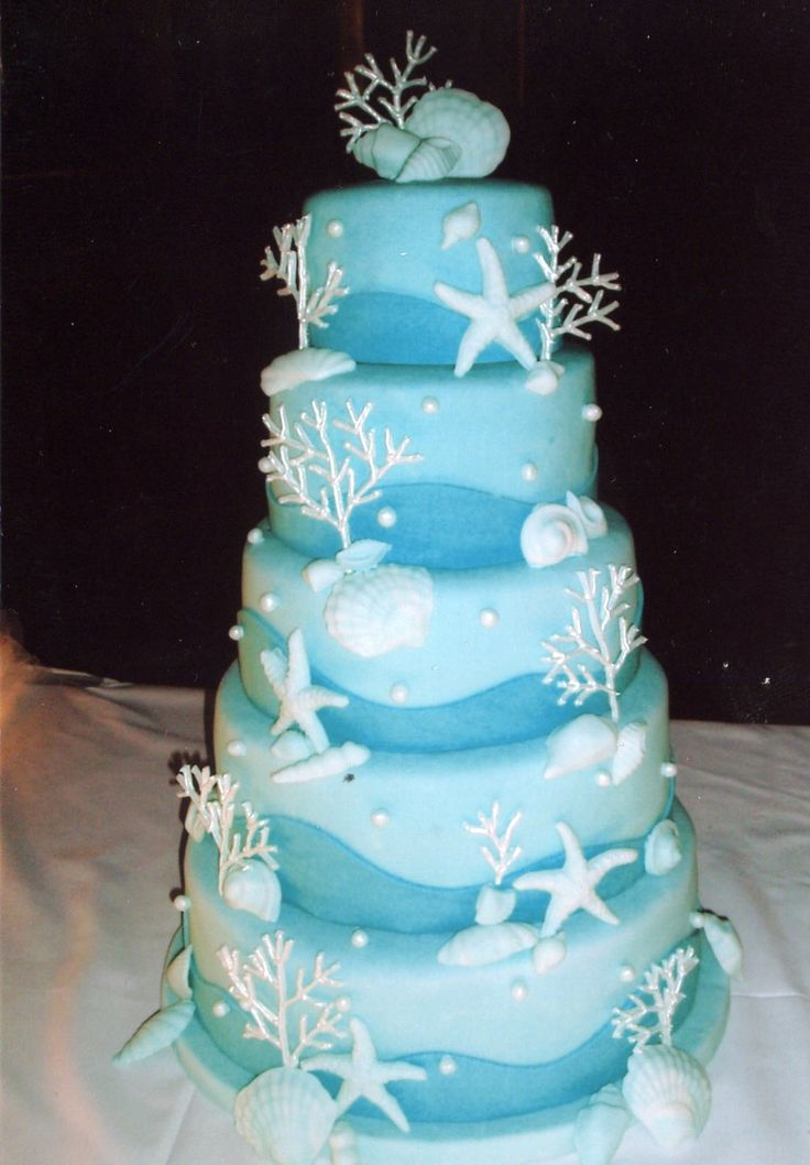 Beautiful blue ocean cake with white starfish, shells and coral