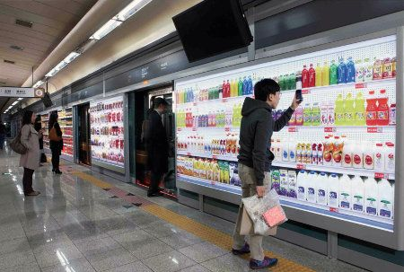 Can Virtual Stores Make Shopping More Sustainable?  Online shopping is starting to collide with the physical world. In Korea, a supermarket chain designed a new shopping experience for subway riders: while they waited on the platform, commuters could look at giant images of store shelves, order items through their phone, and set delivery to happen when they got home from the train. In the photo above, what look like shelves are just photographs with QR codes on the walls of the subway…