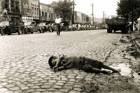 Seoul:  A boy lying on the street near Yeoncheon School (연천초등학교), 1956