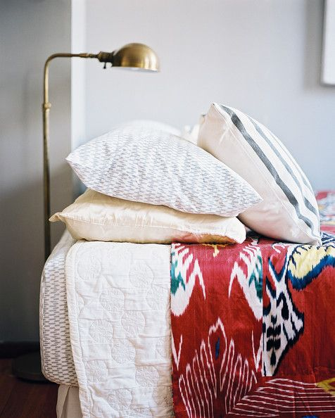 A brass floor lamp beside a bed outfitted with patterned bedding  Details: White Bohemian-Vintage Bedroom  Keywords: Ikat, August September 2010 Issue, Callie Jenschke, Brass Lamp  (Source: Lonny)