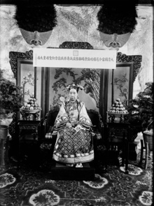 "Empress Dowager Cixi is shown sitting on her throne inside her bedroom chamber, the Hall of Happiness and Longevity of the Summer Palace. The plaque hanging above Cixi is inscribed with her title in full, literally translated as ""The Current Holy Mother Empress Dowager of the Great Qing Empire, Cixi (kind and auspicious) Duanyou (upright and blessed) Kangyi (healthy and well-maintained) Zhaoyu (clear and pleasant) Zhuangcheng (solemn and sincere) Shougong"