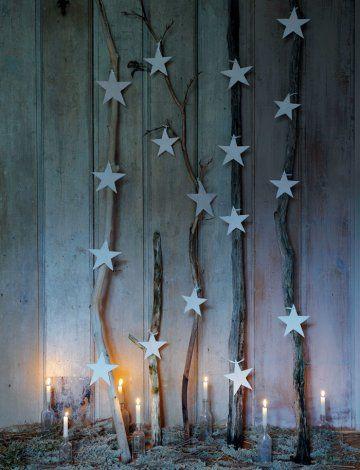 Des étoiles en pâte autodurcissante,  suspendues à des branches de bois de différentes formes et tailles, adossées au mur. A l'intérieur comme à l'extérieur de la maison !