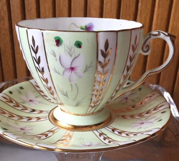Pretty vintage green and gold bone china tea cup and saucer. Royal Grafton Studio Craft marked on the back. Ribbed and foot d tea cup with purple flowers on white background. Cup measures 3 3/8 inches in diameter and about 3 inches tall. Saucer is about 5 1/2 inches in diameter.